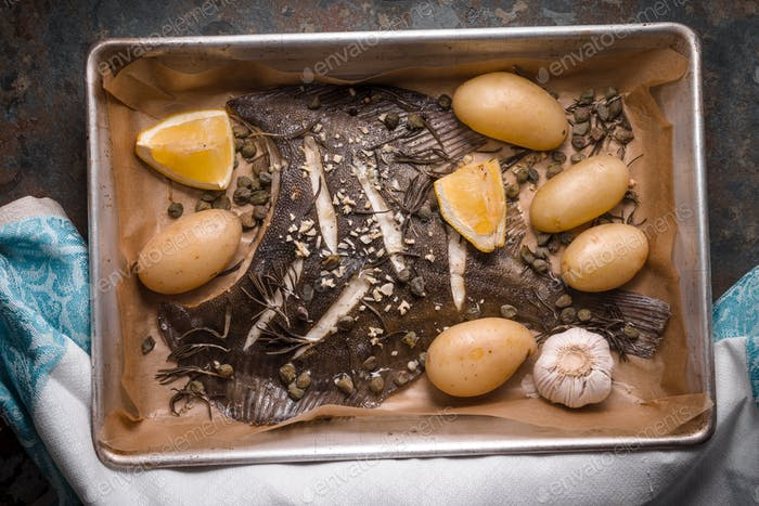 Baked flounder with potato and seasoning in the backing dish on the stone table top view