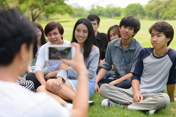 Happy young group of friends taking picture with phone together at the park