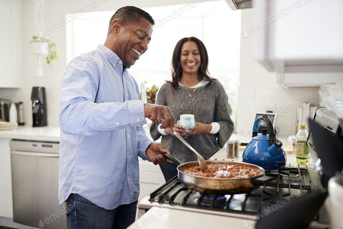 Man standing in the kitchen cooking with his partner standing beside him, backlit
