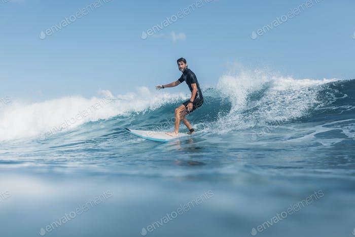 Sportler surft Welle auf Surfbrett im Ozean