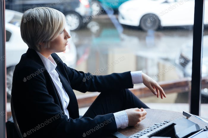 Pretty blonde girl thinking about something in cafe