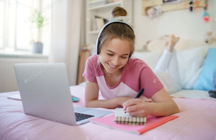 Young female student with laptop on bed, online lesson concept