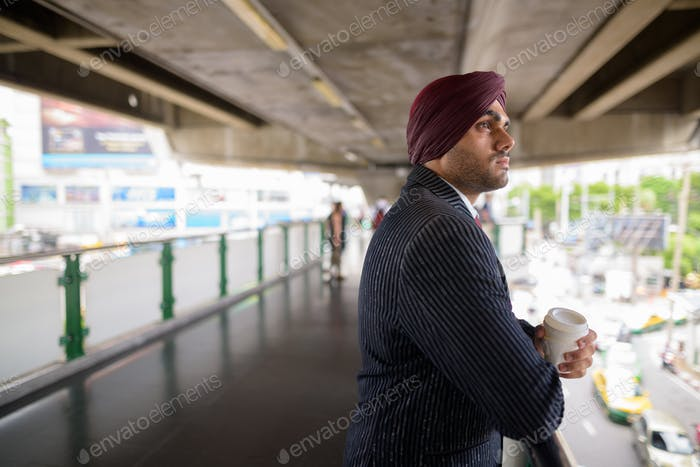 Young handsome Indian Sikh businessman wearing turban outdoors in city