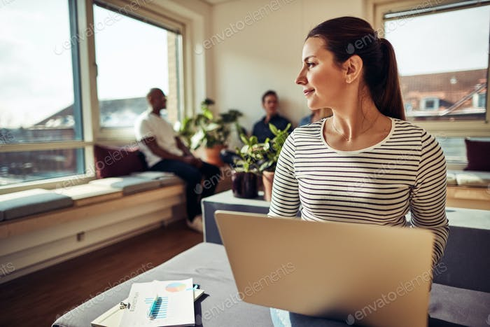 Businesswoman working on a laptop with colleagues in the background