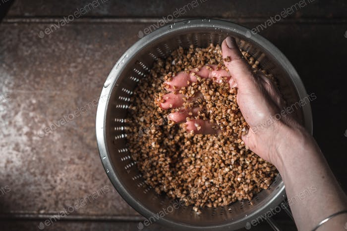 Hand with buckwheat in the metal  colander   top view