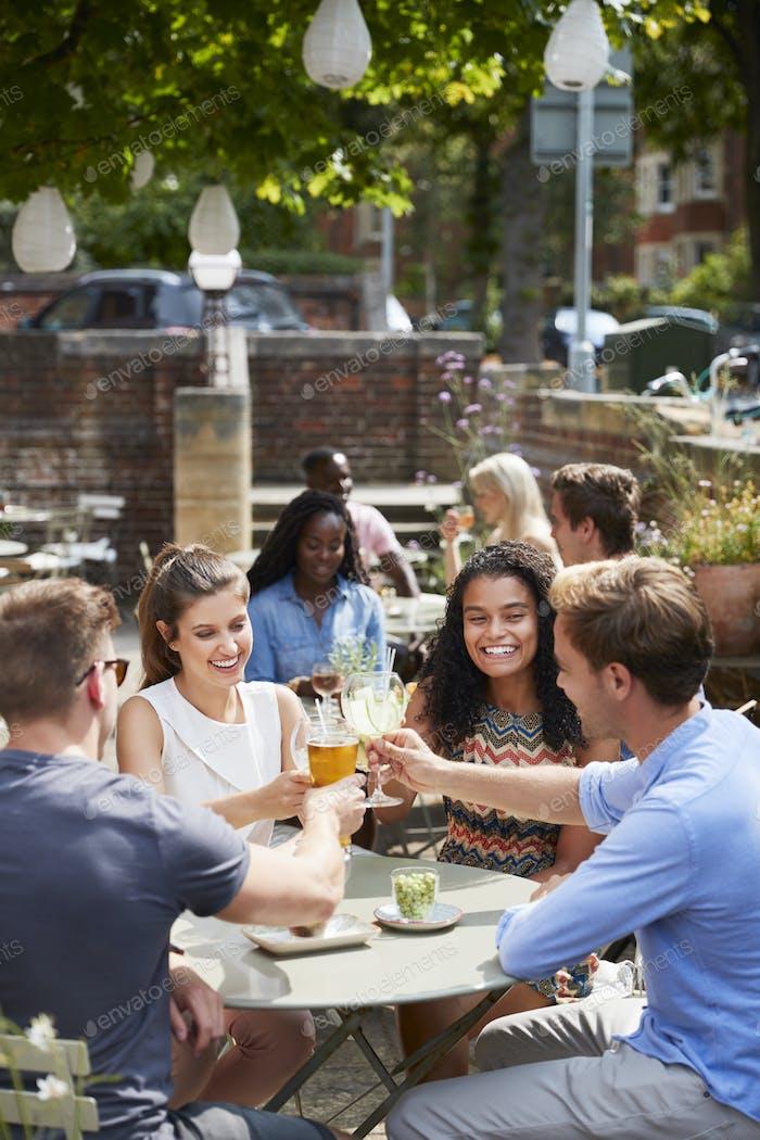 Freunde sitzen am Tisch in Pub Garten machen Toast zusammen