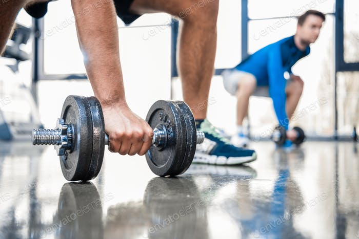 young men workout with dumbbells at gym, focus on man holding dumbbell