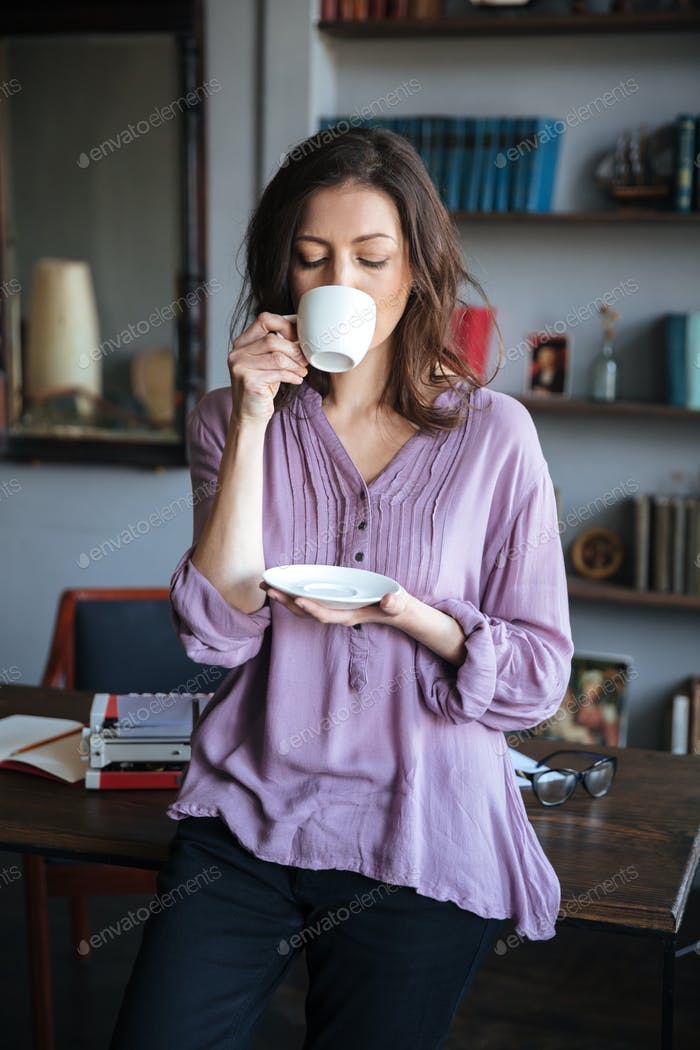 Woman drinking tea while leaning on the table at home