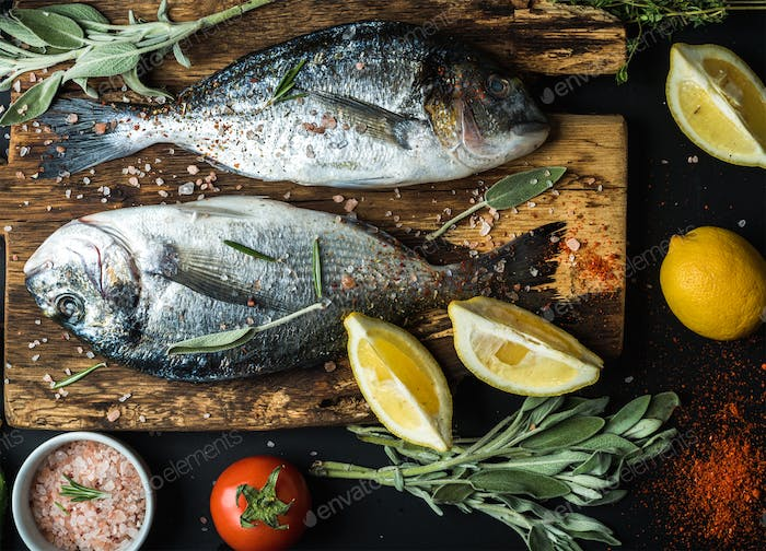 Fresh uncooked dorado or sea bream fish with lemon, herbs, oil, vegetables and spices