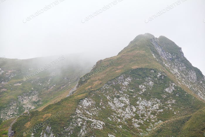 mountain peak in dense fog