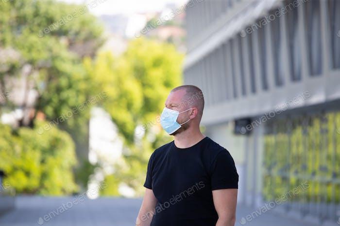 Porträt von brünetten Mann in einer medizinischen chirurgischen Maske in der Stadt.