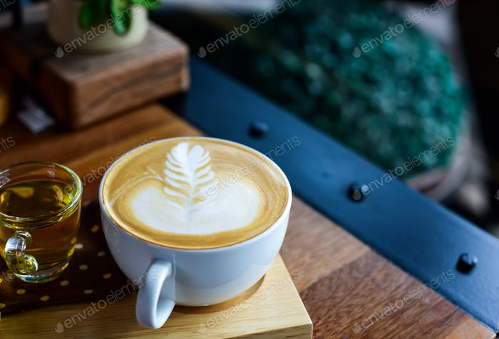 Latte coffee in white mug on wooden tray.