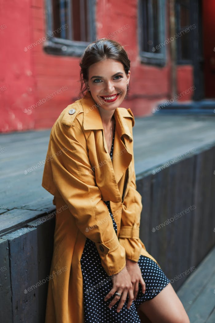 Young beautiful joyful woman in orange trench coat and black pol