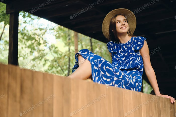 Young attractive smiling woman in blue dress and hat joyfully looking aside in city park