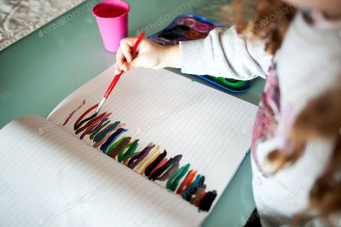 Hände des kleinen Mädchens Malerei mit Aquarellen zu Hause. Lernen, Bildung, glückliche Kindheit Konzept.