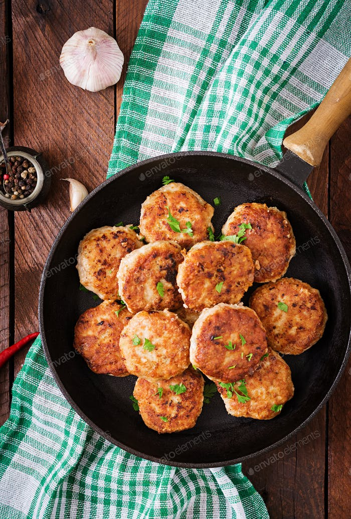 Juicy delicious meat cutlets in pan on a wooden table. Top view