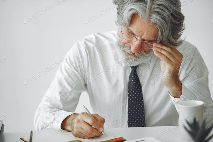 Красивый задумчивый зрелый бизнесмен сидит в офисе