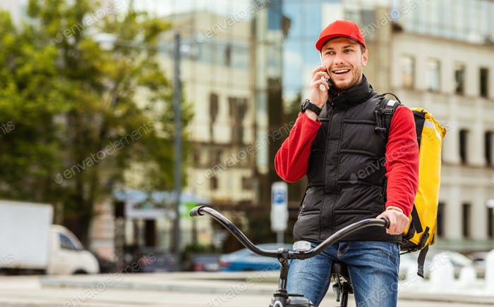 Delivery Guy Talking On Cellphone Delivering Food In City
