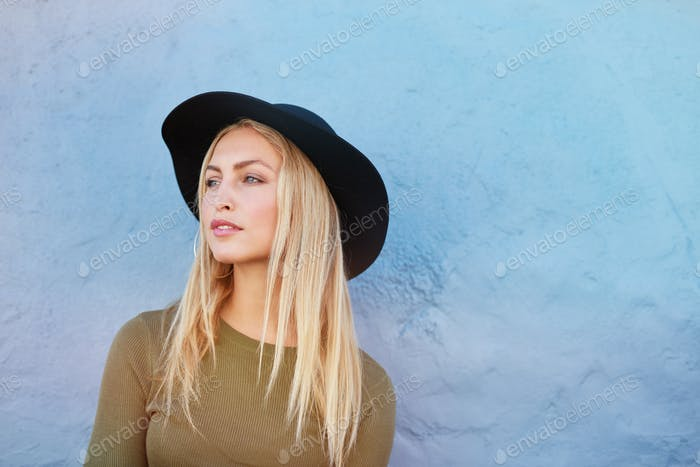Attractive young female model with hat looking away
