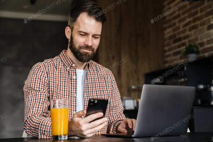 Happy mid aged brunette bearded man sitting at the table