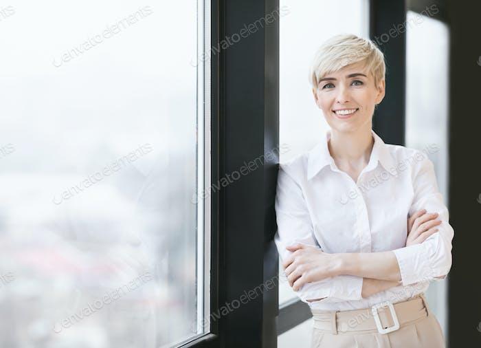 Lächeln Reifen lady Überquerung Hände stehen in der Nähe Fenster in Büro