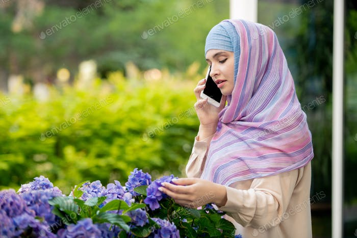 Young muslim woman in hijab talking on smartphone by flowerbed