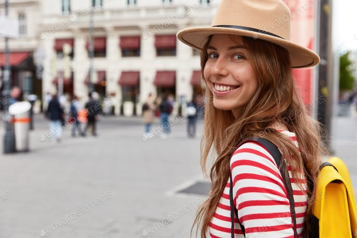 Horizontal view of delighted female tourist walks on street, wears stylish headgear and striped jump