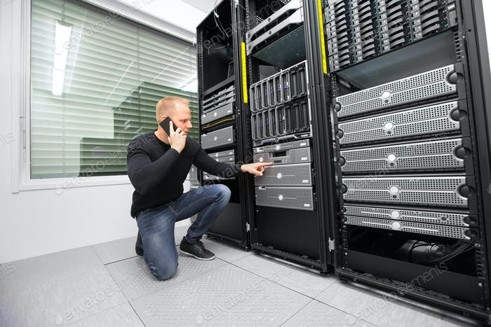 Consultant Using Smartphone While Monitoring Servers In Datacent