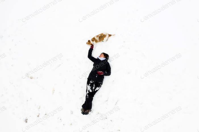 Woman in white snow with her dog, drone view. Friendship concept.