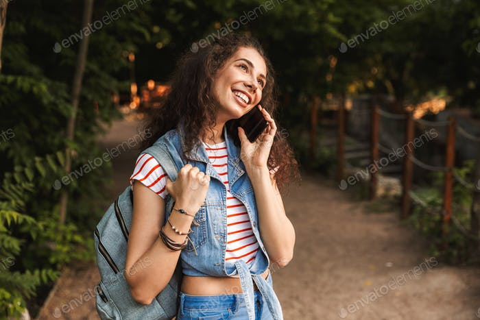 Photo of young brunette student 18-20 wearing backpack, smiling