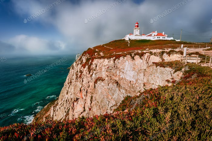 Cabo da Roca Lighthouse at sunlight and beautiful cloudscape. Most westerly point of the Europe