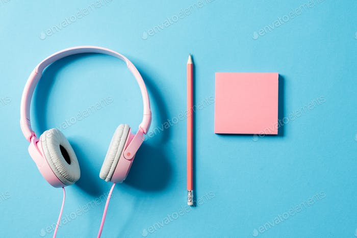 Set of a headphones, a paper and a pencil lying in a studio