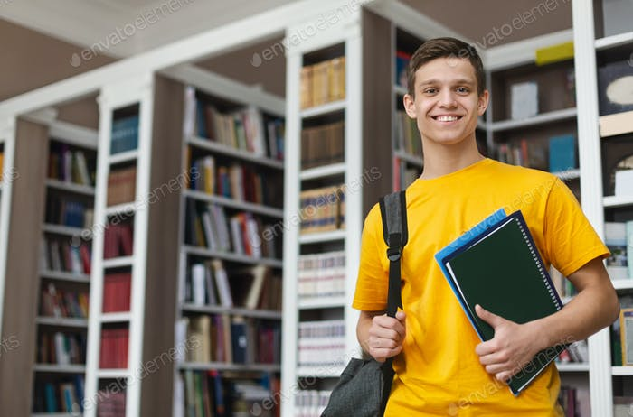 Smiling guy posing in library, holding books and notes