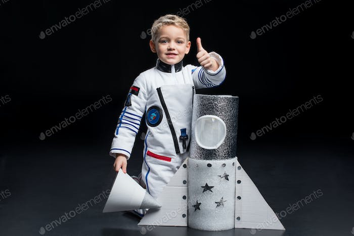Smiling little boy astronaut in space suit kneeling near toy spaceship and showing thumb up