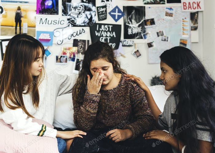 Teenage girls consoling their depressed crying troubled friend