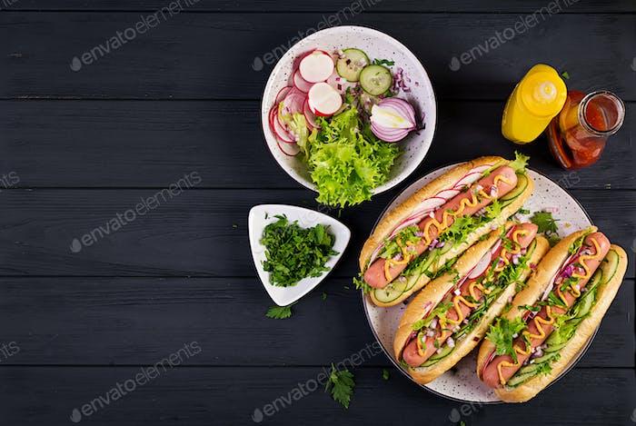 Hot Dog mit Wurst, Gurke, Rettich und Salat auf dunklem Holzhintergrund.