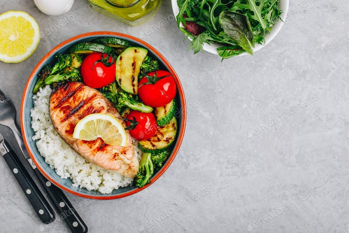 Healthy lunch bowl with grilled salmon, rice and vegetables.