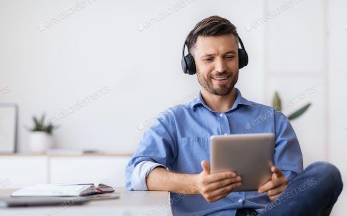 Handsome Businessman In Headphones Relaxing At Workplace With Digital Tablet, Having Break