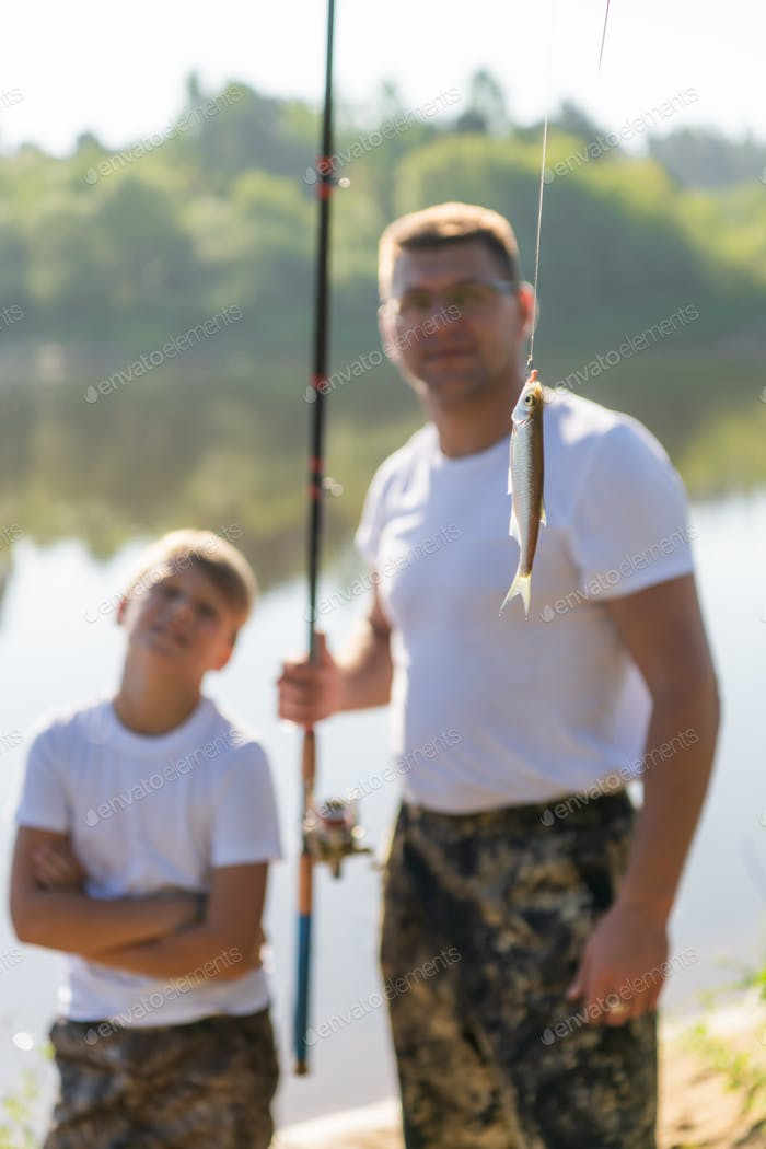 Such a small fish. Father and son stretching a fishing rod with fish on the hook while little boy