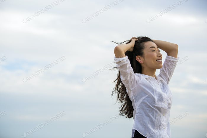 A woman with her hands in her windblown hair on a beach