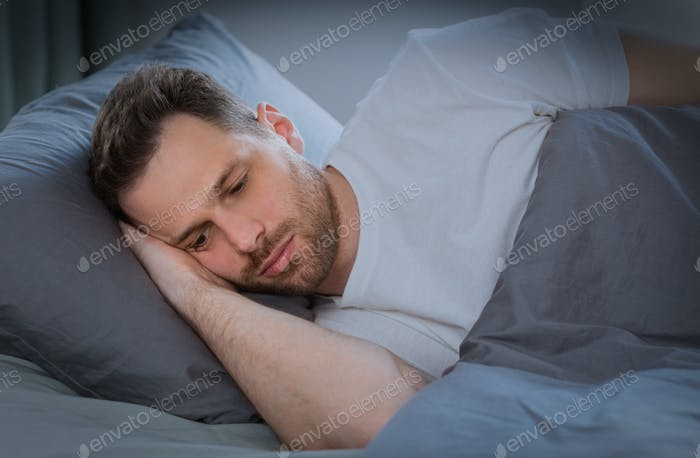 Depressed Man Having Insomnia Lying In Bed At Home