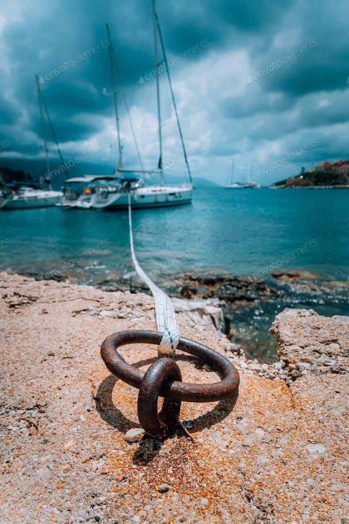 Festmacherseil und Poller auf Meerwasser und Yacht im Hintergrund. Dramatisch Regenwolken darüber