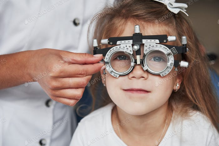 Doctor checking little girl sight and tuning the phoropter