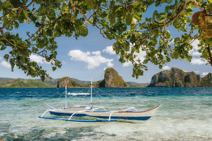 Banca boat in shallow blue water on Ipil beach of Pinagbuyutan Island, El Nido, Palawan, Philippines