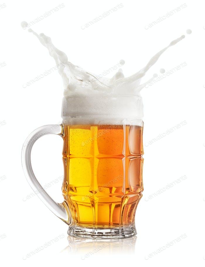 Schaumiger Spritzer von hellem Bier in facettiertem Becher