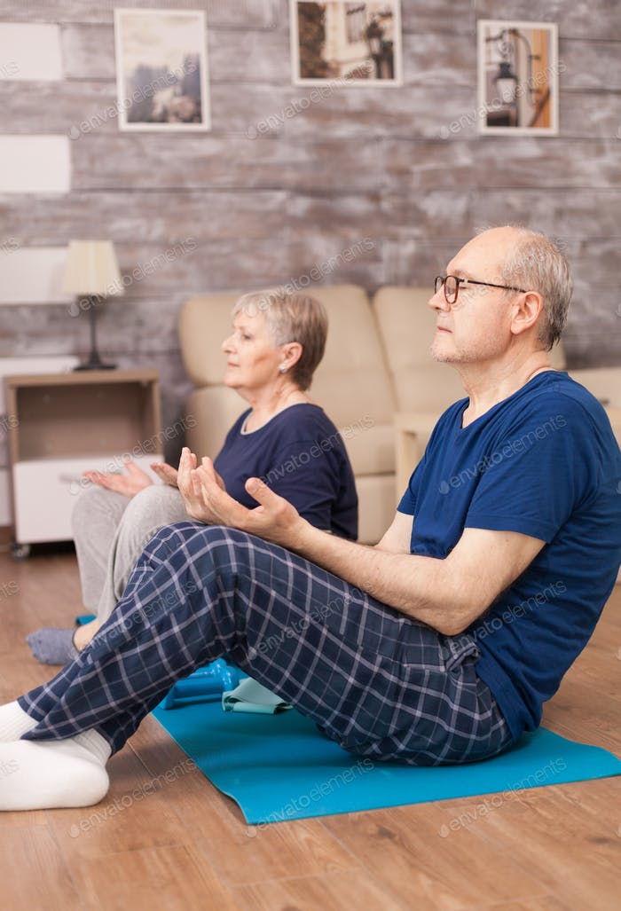 Retired people meditating on yoga mat
