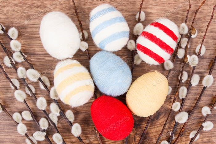 Easter catkins and eggs wrapped woolen string on rustic board, festive decoration