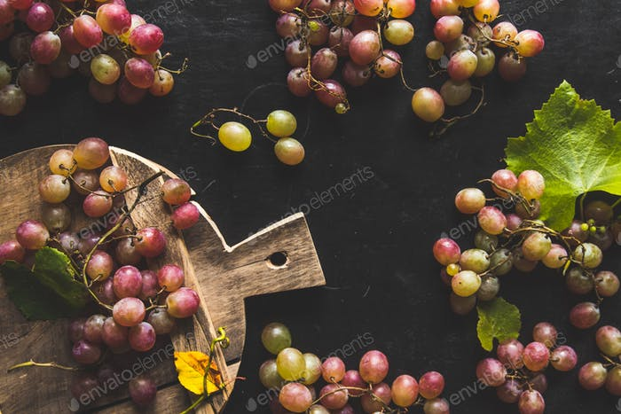 Assortment of fresh grape on cutting board. Grey wooden background