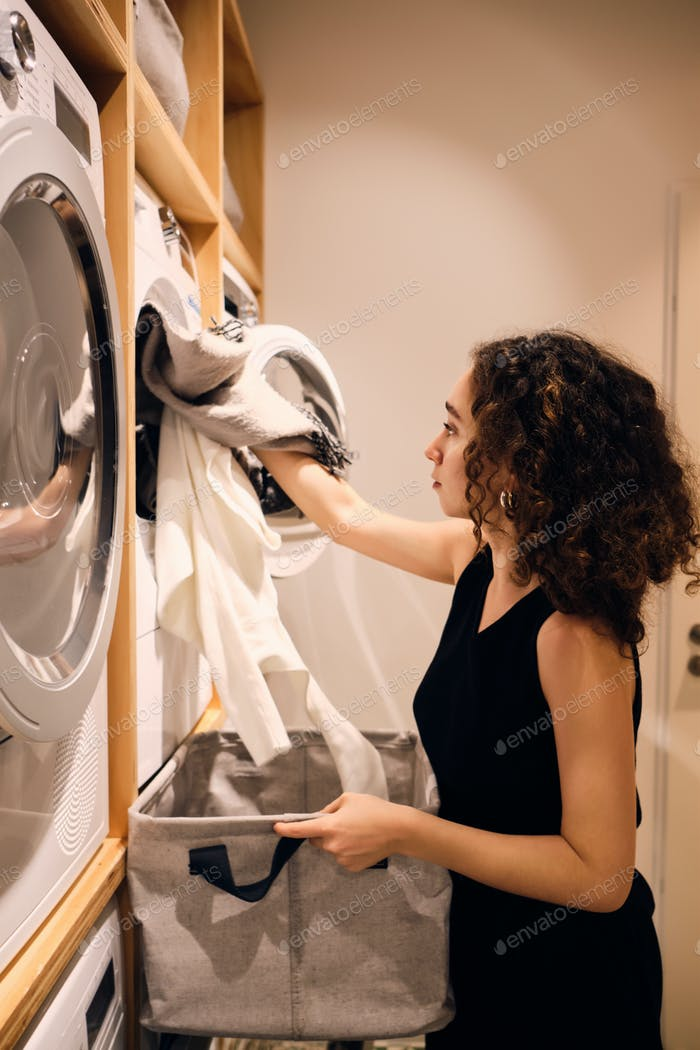 Vista lateral de la chica atractiva cargando ropa en lavadora en lavandería moderna de autoservicio