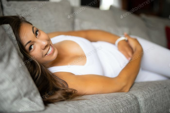 Happy pregnant woman lying on the sofa with her hands at belly